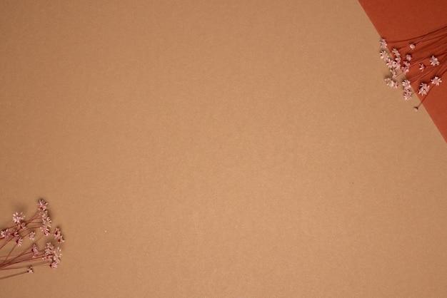 Trockener blumenzweig auf hellbraunem hintergrund. trend, minimal getrocknetes konzept mit copyspace-draufsicht Premium Fotos