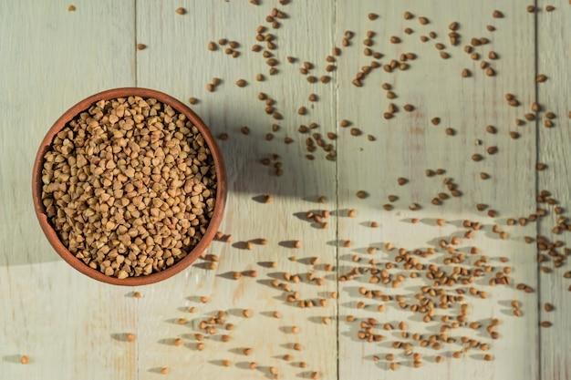 Trockener buchweizen in der braunen lehmschüssel auf holztisch. glutenfreies getreide für gesunde ernährung, ansicht von oben Premium Fotos