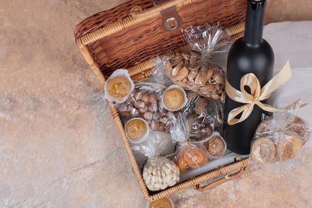 Trockenfrüchte und nüsse in holztasche mit flasche wein. Kostenlose Fotos