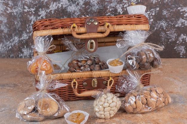 Trockenfrüchte und nüsse in plastiktüten mit holztasche verpackt. Kostenlose Fotos