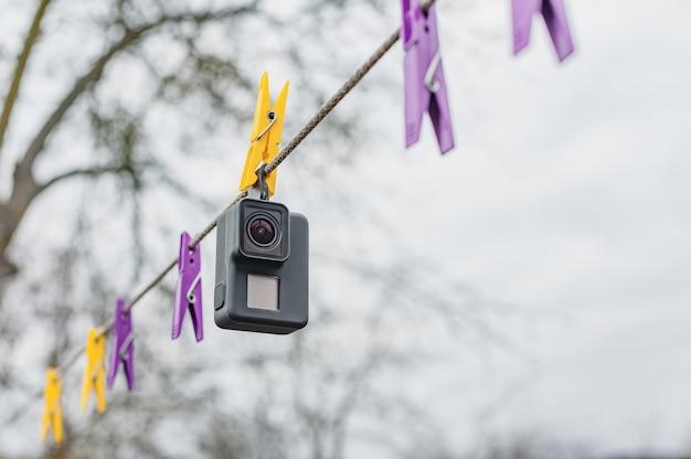 Trocknende wasserdichte action-kamera auf wäscheklammern, gegen den himmel. Premium Fotos