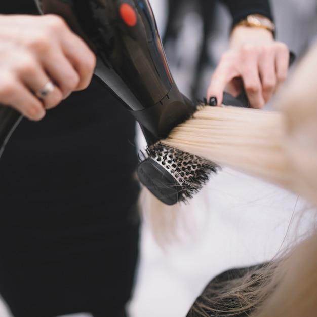 Trocknendes haar des anonymen stylisten mit bürste Kostenlose Fotos