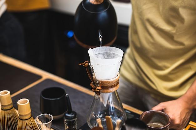Tropfbrühen, gefilterter kaffee oder übergießen sind methoden, bei denen wasser über geröstete, gemahlene kaffeebohnen in einem filter gegossen wird Premium Fotos