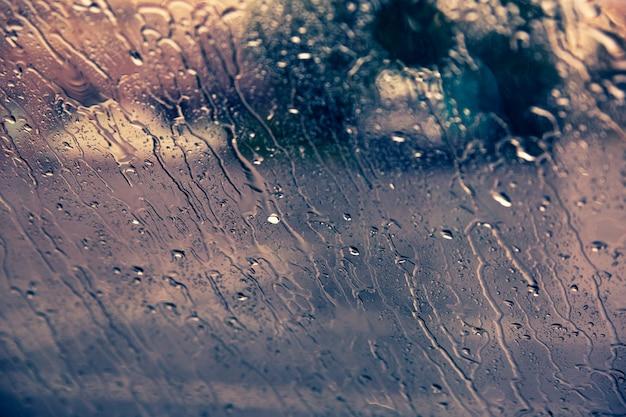 Tropfen des regens auf autowindschutzscheibenhintergrund unten fließen Premium Fotos