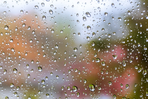 Tropfen des regens auf blauem glashintergrund. straße bokeh leuchtet unscharf. Premium Fotos