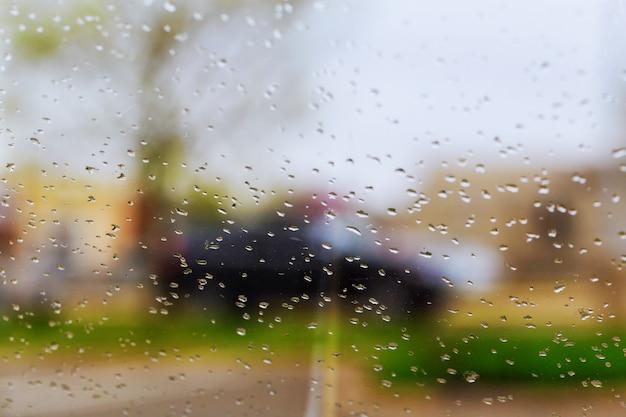 Tropfen des regens auf blauem glashintergrund. straße bokeh lichter unscharf. Premium Fotos