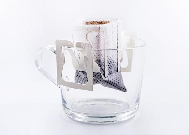 Tropfen sie frischen beutel kaffee auf ein glas Premium Fotos