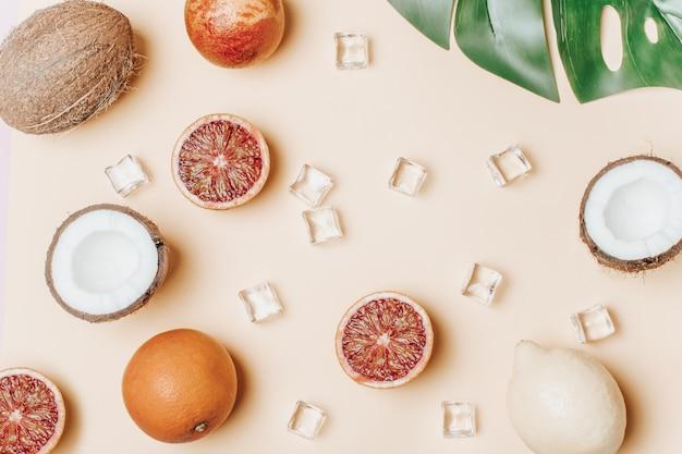 Tropische früchte, blutorangen, kokosnuss, palmblatt Premium Fotos