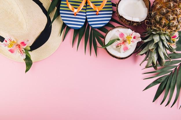 Tropische palmblätter, hut, hausschuhe, ananas, kokosnuss auf weißem hintergrund. Premium Fotos