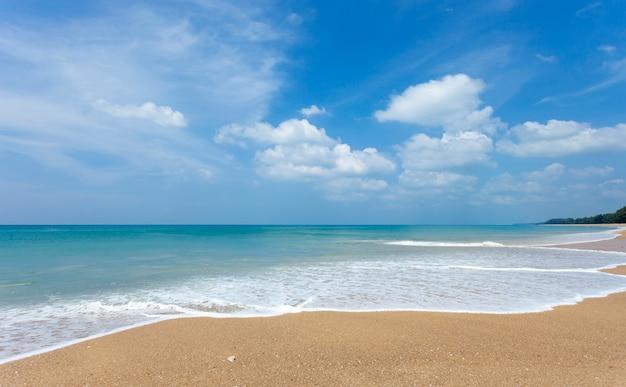 Tropischer sandiger strand mit hintergrund des blauen ozeans und des blauen himmels Premium Fotos