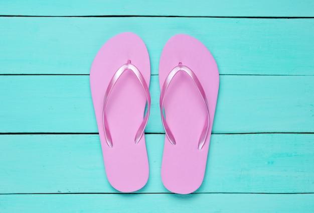 Tropischer strandlebensstil. flip flops auf blauem holzhintergrund. sommerhintergrund. draufsicht Premium Fotos