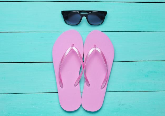 Tropischer strandlebensstil. flip flops und sonnenbrille auf blauem holzhintergrund. sommerhintergrund. draufsicht Premium Fotos