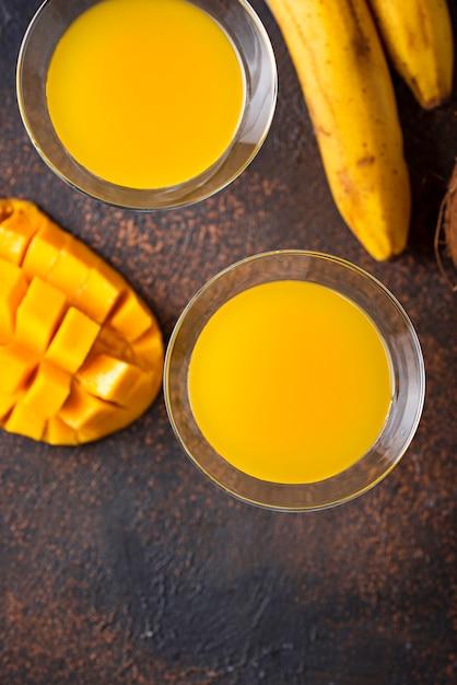 Tropisches cocktail mit mango auf dunklem hintergrund Premium Fotos