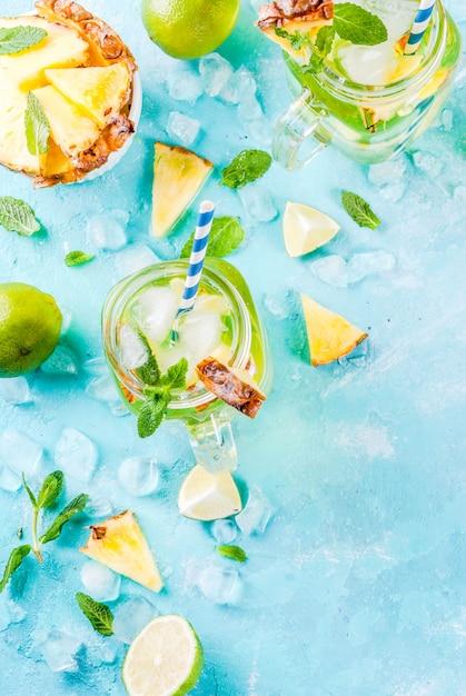 Tropisches getränk ananas mojito oder limonade mit hellblauem hintergrund des frischen kalkes und der minze Premium Fotos