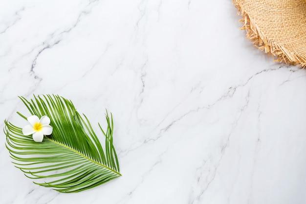 Tropisches palmblatt, großer strohhut, blume auf weißem marmor Premium Fotos