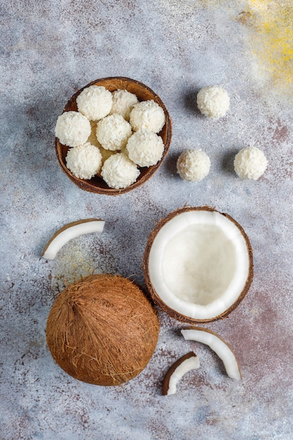 Trüffel aus kokosnuss und weißer schokolade mit halber kokosnuss Kostenlose Fotos