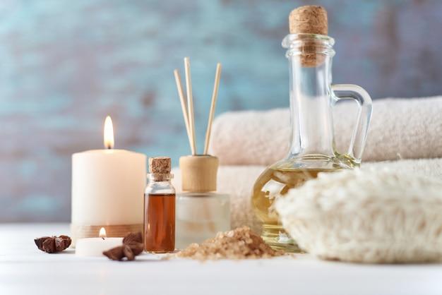 Tücher, kerze und massageöl auf weißer tabelle Premium Fotos