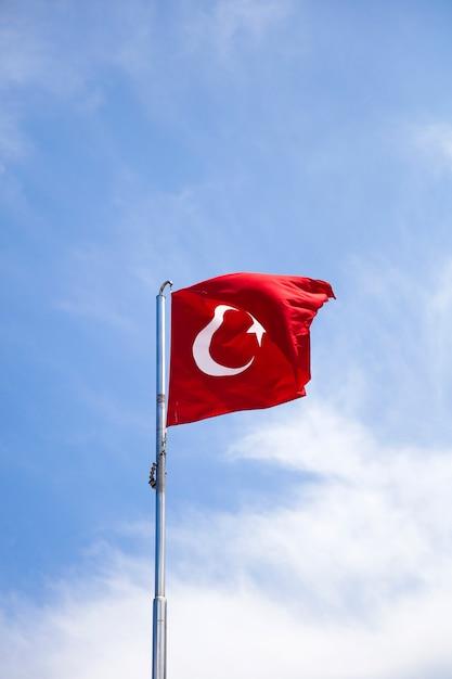 Türkische flagge, die in den wind am blauen himmel wellenartig bewegt Premium Fotos