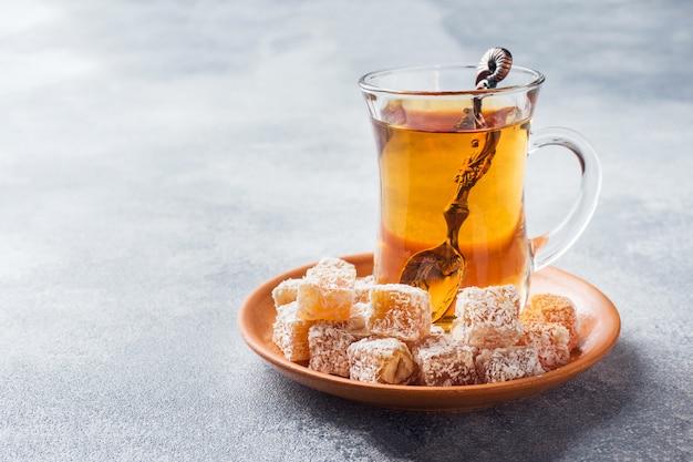 Türkische freude mit haselnuss in geschnitzter metallschale und tee in glasschale Premium Fotos