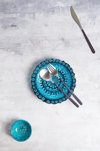 Türkische keramik verzierte blaue platte und schüssel mit neuem schwarzem luxusbesteck Premium Fotos