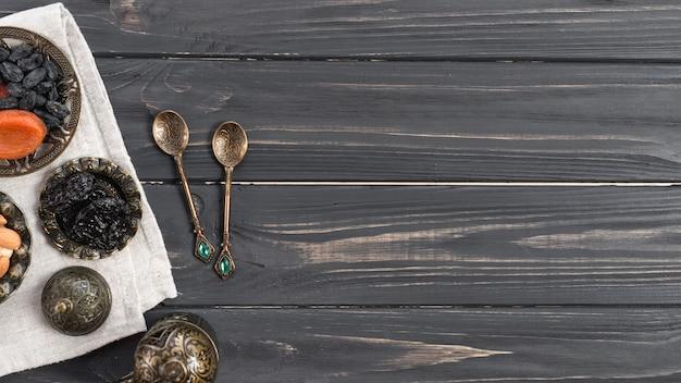Türkische metalllöffel mit getrockneten datteln; rosine über dem hölzernen schreibtisch Kostenlose Fotos