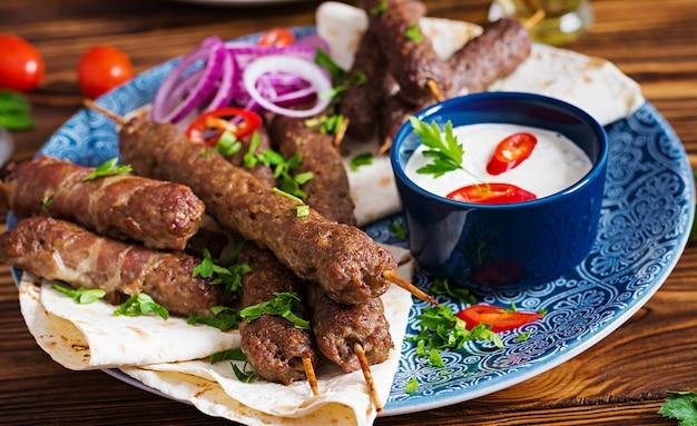 Türkische und arabische traditionelle ramadan-mischungskebabplatte. kebab adana, huhn, lamm und rindfleisch auf lavashbrot mit soße. ansicht von oben Kostenlose Fotos