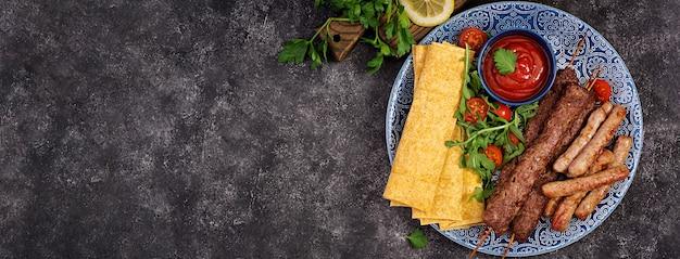 Türkische und arabische traditionelle ramadan-mischungskebabplatte. kebab adana, lamm und rindfleisch auf lavaschbrot mit tomatensauce. ansicht von oben Premium Fotos