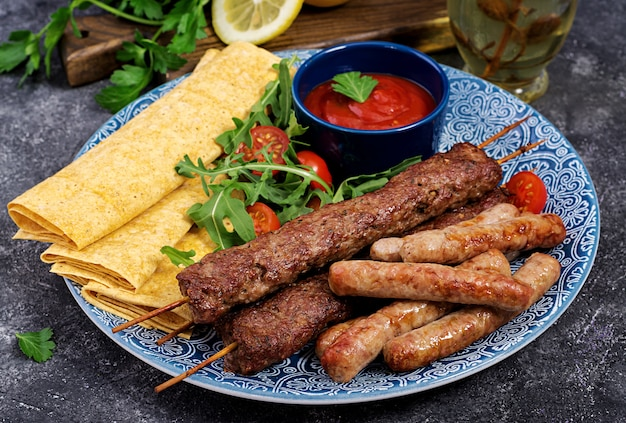 Türkische und arabische traditionelle ramadan-mischungskebabplatte. kebab adana, lamm und rindfleisch auf lavaschbrot mit tomatensauce. Premium Fotos