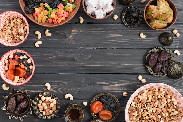 Türkisches dessert baklava; lukum mit trockenfrüchten und nüssen auf holztisch mit kopienraum in der mitte Kostenlose Fotos