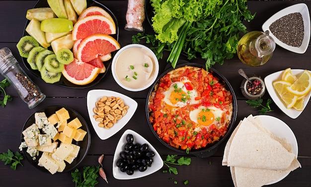 Türkisches frühstück - shakshuka, oliven, käse und obst. Premium Fotos