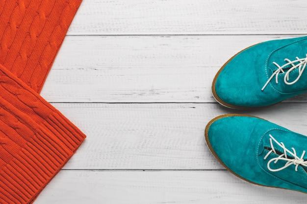 Türkisfrauen schnüren sich schuhe und orange gestrickte strickjacke auf hölzernem hintergrund. Premium Fotos