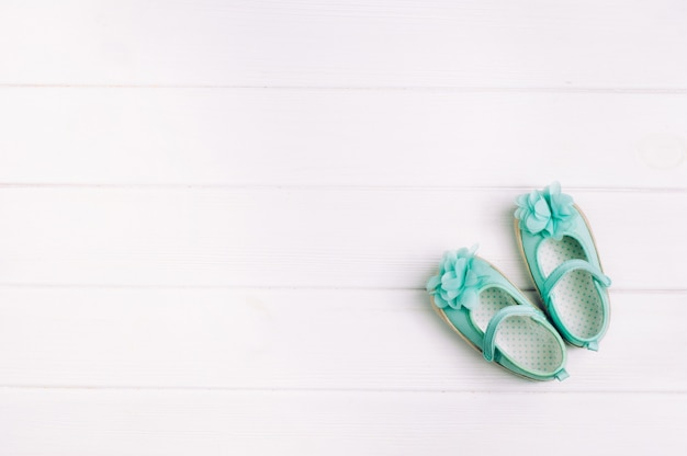 Türkisschuhe für baby über hellem hölzernem hintergrund mit kopienraum Premium Fotos