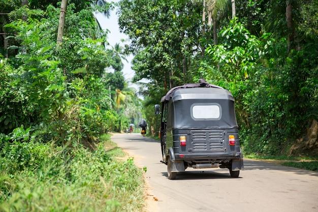 Tuk tuk auf der straße von sri lanka, rückansicht. ceylon tropenwald und traditioneller touristentransport Premium Fotos