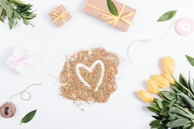 Tulpen, kästen mit geschenken und bänder um die süßigkeit in der herzform Premium Fotos