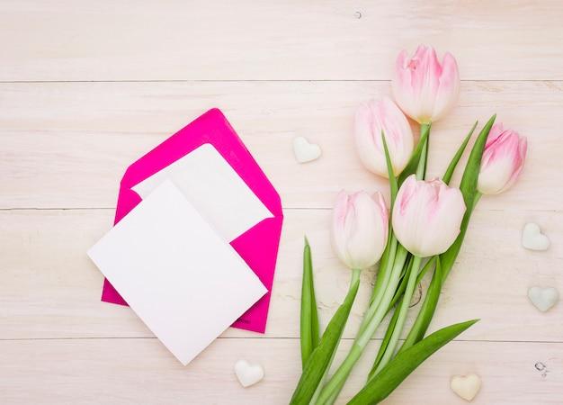Tulpen mit leerem papier und umschlag Kostenlose Fotos