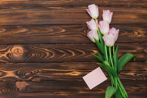 Tulpen und karte mit leerem aufkleber auf dunkler tabelle Kostenlose Fotos