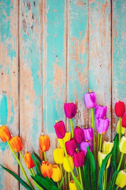 Tulpenblüte blüht auf hölzernem hintergrund der weinlese, grenzrahmendesign. weinlesefarbton - konzeptblume des frühlings- oder sommerhintergrundes Premium Fotos