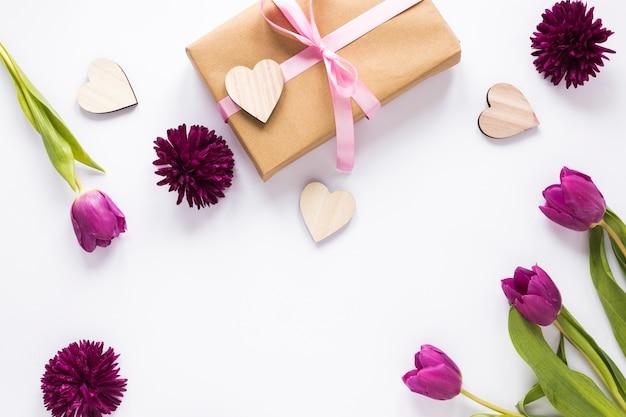 Tulpenblumen mit geschenkbox und hölzernen herzen Kostenlose Fotos