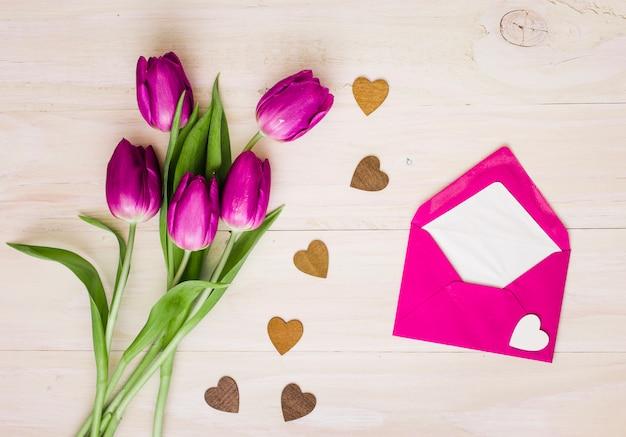Tulpenblumen mit umschlag und kleinen herzen Kostenlose Fotos