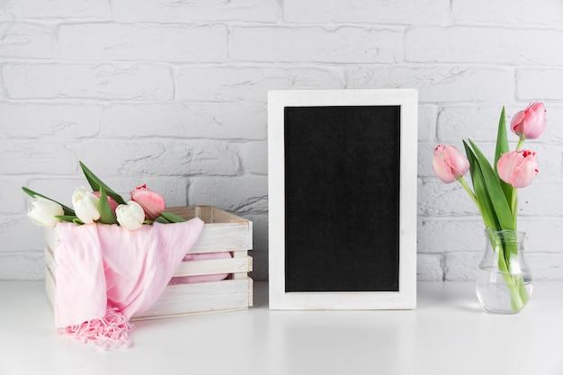 Tulpenvase und -kiste nahe dem leeren schwarzen weißen grenzrahmen auf schreibtisch gegen backsteinmauer Kostenlose Fotos