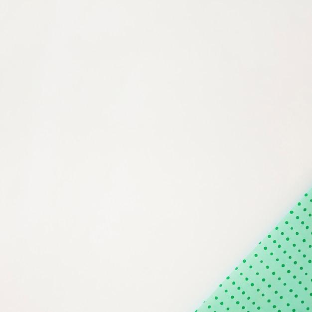 Tupfengrün wickelte papier auf der ecke des weißen hintergrundes ein Kostenlose Fotos