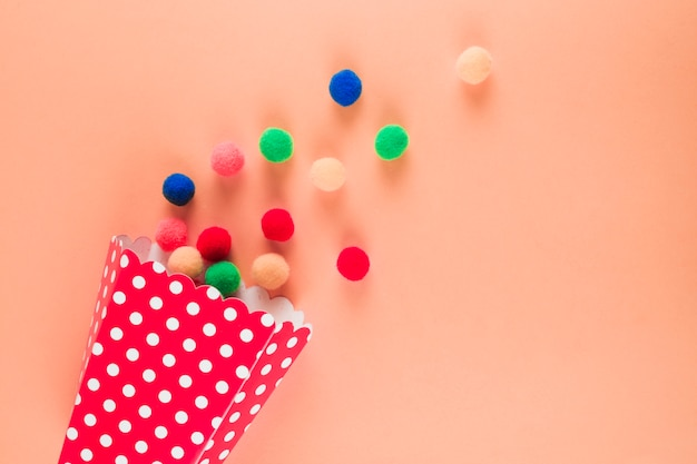 Tupfenkegel mit verschütteten bunten garnbällen auf pfirsich färbte hintergrund Kostenlose Fotos