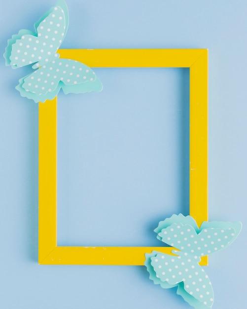 Tupfenschmetterling auf gelbem grenzrahmen über blauem hintergrund Kostenlose Fotos