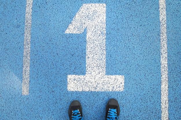 Turnschuhe auf spur nr. 1. blaues sportfeld mit der bedeutung, im sport erfolgreich zu sein Premium Fotos