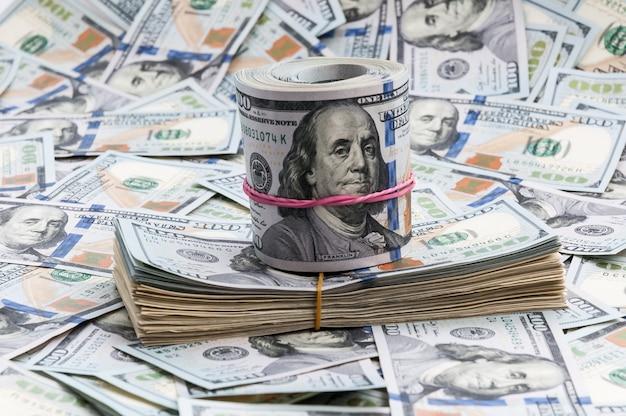 Tutu und rolle von dollar auf einem hintergrund von rechnungen von hundert dollar. Premium Fotos