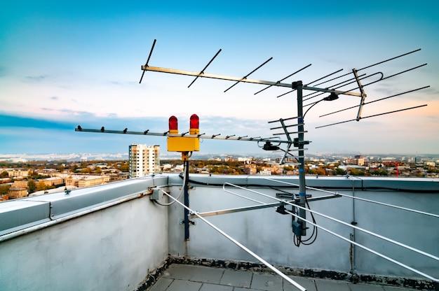 Tv-antenne auf dem dach eines mehrstöckigen gebäudes Premium Fotos