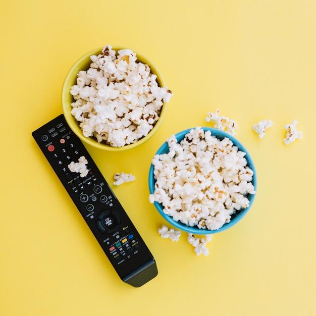 Tv-fernbedienung in der nähe von schüsseln mit popcorn Kostenlose Fotos