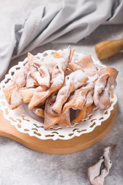 Typisch italienische karnevalskrapfen mit puderzucker auf betontisch bestäubt. Premium Fotos