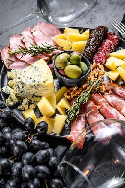 Typische italienische antipasti mit schinken, schinken, käse und oliven. ansicht von oben Premium Fotos