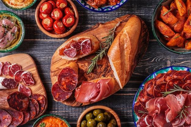 Typisches spanisches tapas-konzept. das konzept umfasst verschiedene scheiben jamon, chorizo, salami, schalen mit oliven, paprika, sardellen, würzige kartoffeln und kichererbsenpüree Premium Fotos